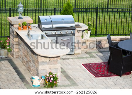 High angle view of a stylish outdoor kitchen on a brick patio with a built in gas barbecue,rug and dining table overlooking a green lawn and railing - stock photo