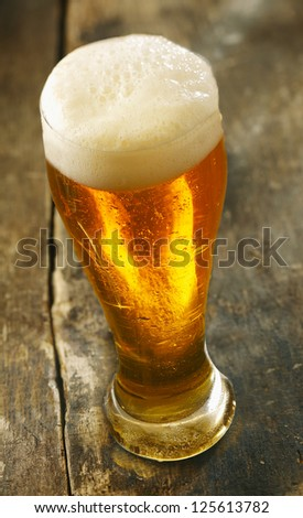 High angle view of a tall glass of chilled beer with a frothy head standing on an old grunge wooden table - stock photo