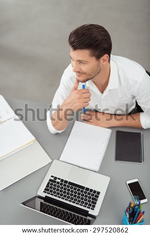 High Angle View of a Young Businessman Sitting at his Desk with Laptop and Notes, Looking Into Distance with a Happy Facial Expression. - stock photo
