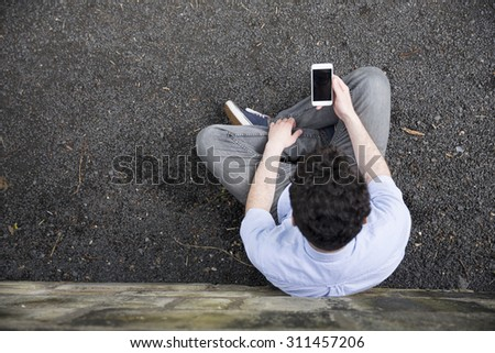 High angle view of a young man using a Smart phone outdoors.   - stock photo