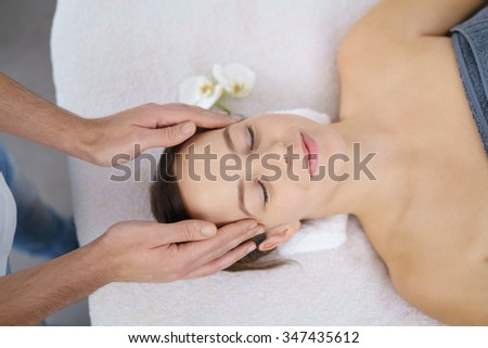 High Angle View of a Young Woman Lying on Bed and Enjoying a Head Massage in the beauty center - stock photo