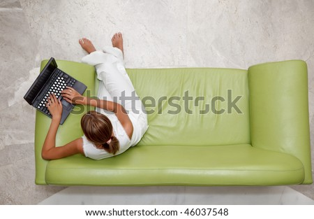 High angle view of a young woman using laptop while sitting on sofa - stock photo
