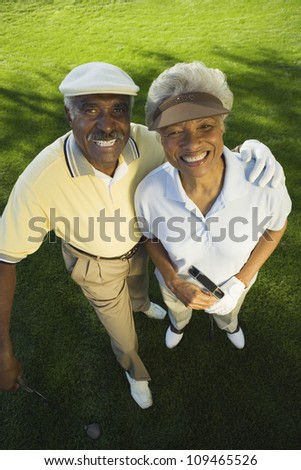 High angle view of an African American couple with arm around on golf course - stock photo