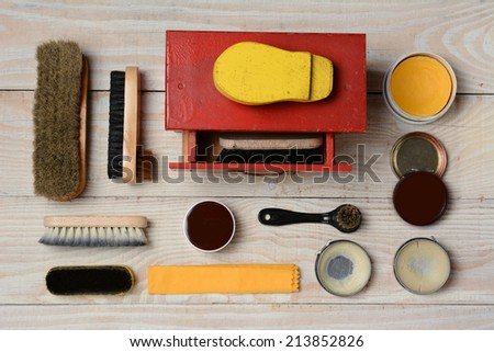 High angle view of  an antique shoe shine kit and its accessories, including brushes, polish, and buffing cloth. Horizontal format on a white wood surface. - stock photo