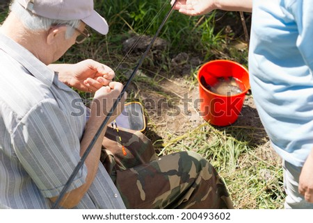 High angle view of an elderly fisherman baiting his hook as a woman stands alongside him supporting the tip of his rod