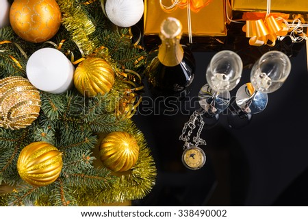High Angle View of Antique Pocket Watch on Black Surface with Bottle of Champagne and Pair of Glasses with Gold Wrapped Gifts and Evergreen Branches Decorated with Christmas Ball and Tinsel - stock photo