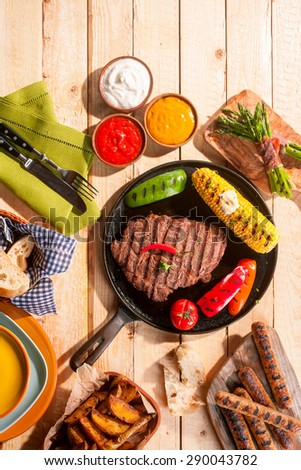 High Angle View of Barbequed Meal Featuring Grilled Steak, Sausage, and Vegetables Served with Dips and Sides on Wooden Picnic Table - stock photo