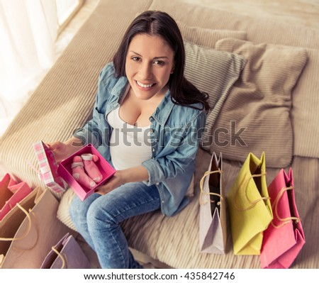 High angle view of beautiful pregnant woman holding a gift box with baby shoes, looking at camera and smiling while sitting on couch at home - stock photo