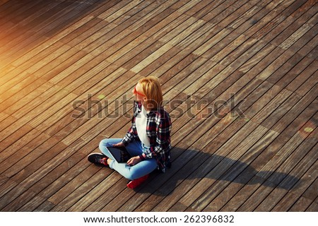 High angle view of beautiful teenager girl sitting with digital tablet looking into the distance, carefree bright future concept,young blond hair student sitting on wooden pier looking away, flare sun - stock photo