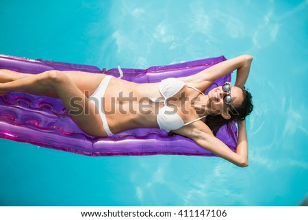 High angle view of beautiful woman relaxing on inflatable raft at swimming pool - stock photo