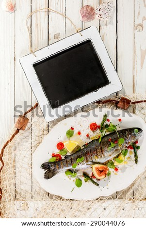High Angle View of Blank Chalkboard on Rustic White Table with Whole Garnished Grilled Fresh Fish on White Platter with Fishing Net - stock photo