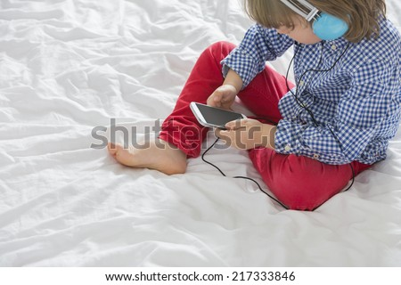 High angle view of boy listening to music through smart phone in bedroom - stock photo