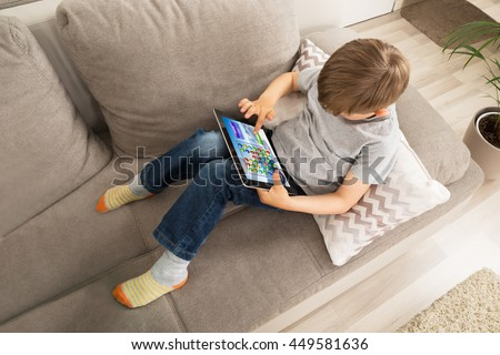High Angle View Of Boy Using Digital Tablet For Playing Game