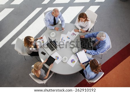 High angle view of business people discussing in a meeting while sitting at conference table. Using digital tablet and computer while analyzing financial data.  Shot taken from directly above.