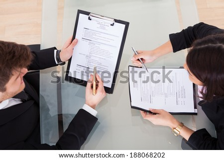 High angle view of business people discussing over documents at desk in office - stock photo