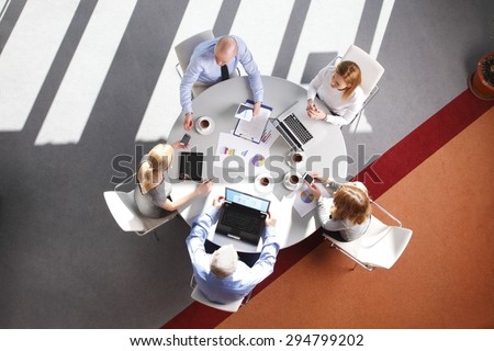 High angle view of business team in a meeting. Businesswomen and businessmen sitting around conference table and working with laptop and digital tablet while consulting.