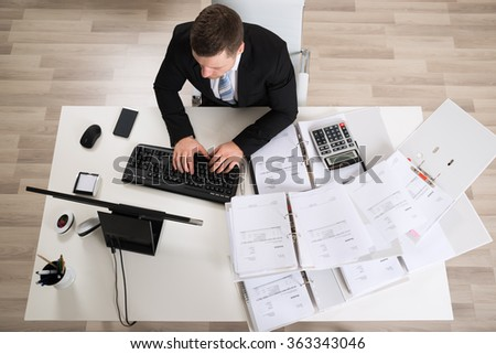 High angle view of businessman analyzing documents at computer desk in office - stock photo