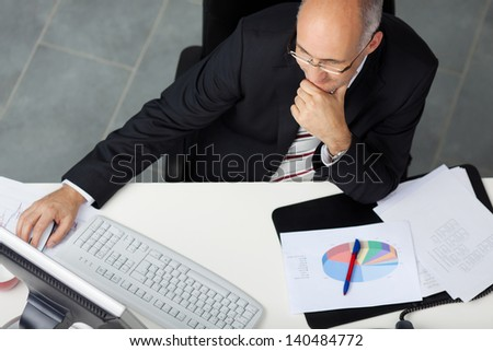 High angle view of businessman using computer at office desk - stock photo