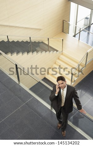 High angle view of businessman using mobile phone while leaning on glass railing in office - stock photo