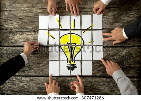 High angle view of businessmen hands touching white papers arranged on a rustic wooden table forming a yellow light bulb. Conceptual for bright business ideas and innovations.  - stock photo