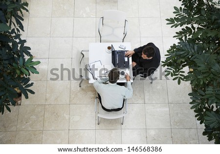 High angle view of businessmen having a discussion at office cafe - stock photo
