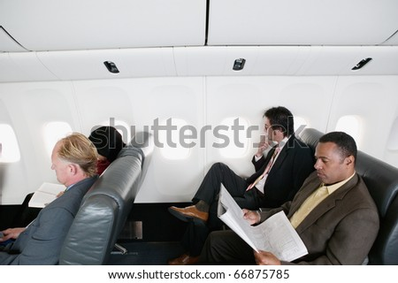 High angle view of businessmen traveling in an airplane - stock photo