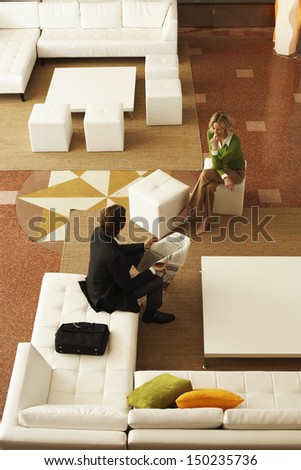 High angle view of businesspeople communicating while sitting in office lobby - stock photo