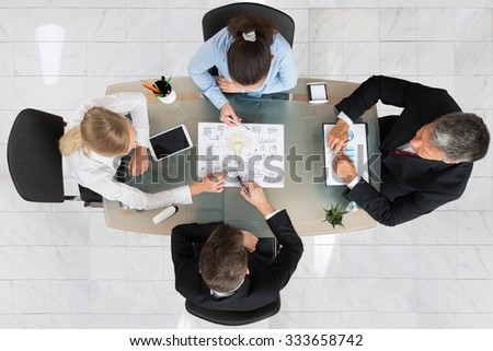 High Angle View Of Businesspeople Discussing Start-up Plan At Desk