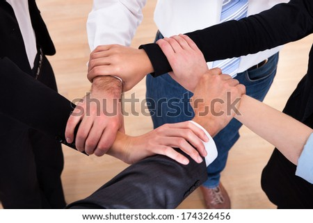 High Angle View Of Businesspeople Holding Wrist - stock photo