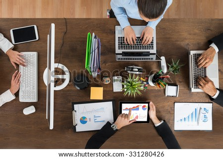 High Angle View Of Businesspeople Working On Electronic Devices At Wooden Desk - stock photo