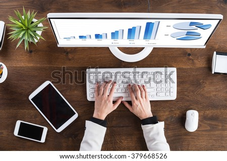 High Angle View Of Businessperson Analyzing Graph On Computer At Desk - stock photo
