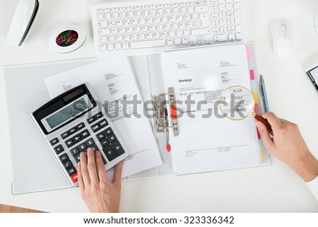 High Angle View Of Businessperson Examining Invoice With Magnifying Glass - stock photo