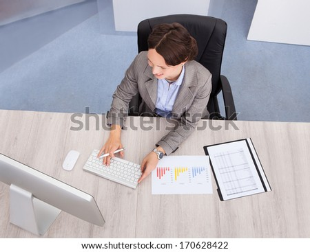 High Angle View Of Businesswoman Smiling Young Businesswoman At Desk - stock photo