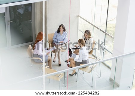 High angle view of businesswomen discussing in office - stock photo
