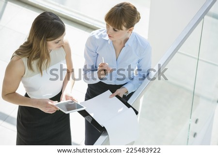 High angle view of businesswomen discussing over tablet PC and documents by railing in office - stock photo