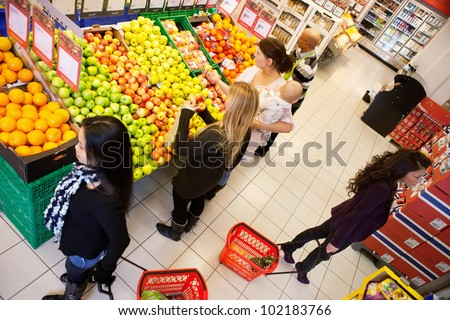 High angle view of busy people shopping in supermarket - stock photo
