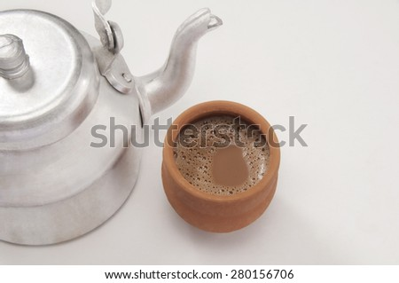 High angle view of chai in traditional cup made of mud with tea kettle isolated over white background - stock photo