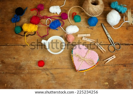 High angle view of coffee, various wool yarns and heart shaped coasters on wooden surface.