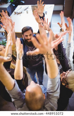 High angle view of creative business people cheering in office - stock photo