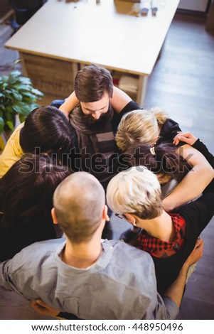 High angle view of creative business people forming huddle in office - stock photo