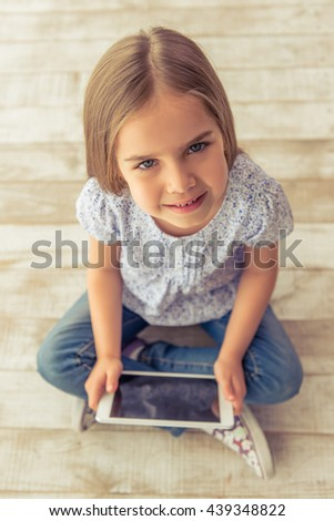 High angle view of cute little girl using a tablet, looking at camera and smiling while sitting on wooden floor - stock photo