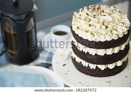 High Angle View of Decadent Chocolate Triple Layer Cake Decorated with White Cream Icing and Shavings Served with Freshly Brewed Coffee in Bodum - stock photo