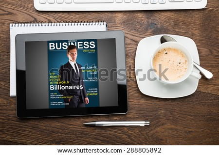 High Angle View Of Digital Tablet Showing Magazine Cover - stock photo