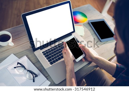 High angle view of editor using smartphone and laptop in creative office - stock photo
