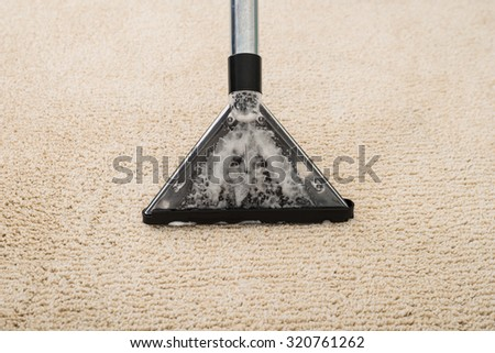 High Angle View Of Electric Vacuum Cleaner Over Carpet With Foam - stock photo