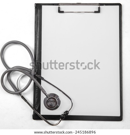 High angle view of empty paper on medical clipboard with stethoscope - stock photo