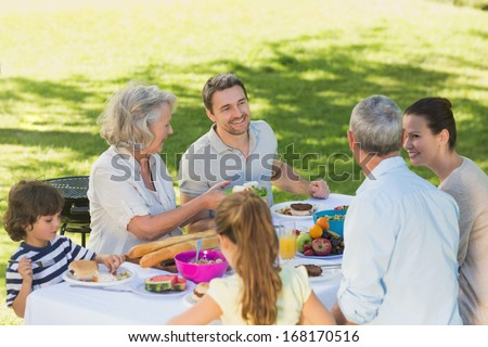 High angle view of extended family dining at outdoor table - stock photo