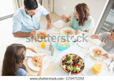 High angle view of family of four sitting at dining table in the home - stock photo
