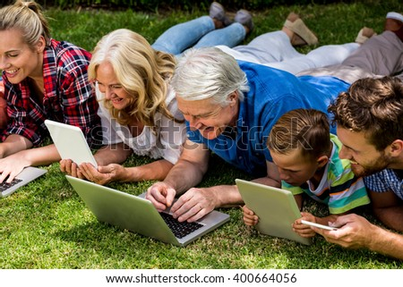 High angle view of family using technologies while relaxing at park - stock photo