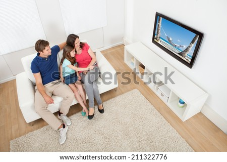 High angle view of family watching TV together while relaxing on sofa at home - stock photo
